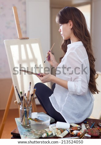 female artist with oil colors and brushes near  easel with blanl canvas ready for job - stock photo