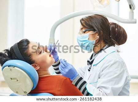 female asian dentist doctor during tooth examination and treatment - stock photo