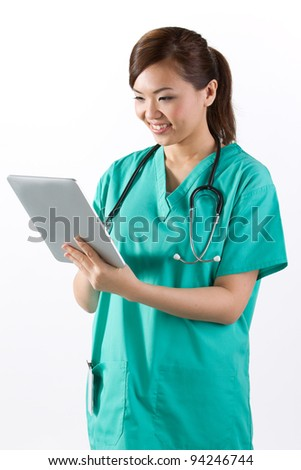 Female Asian doctor looking at a digital tablet & wearing a green scrubs plus stethoscope. - stock photo