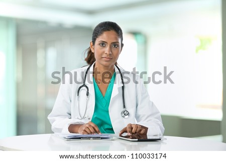 Female Asian doctor sitting at a table using a digital tablet. - stock photo
