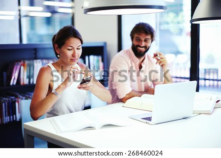 Female asian student take a picture of textbook with her mobile phone while sitting in university library, colleagues at work having fun laughing, young successful business persons using technology - stock photo