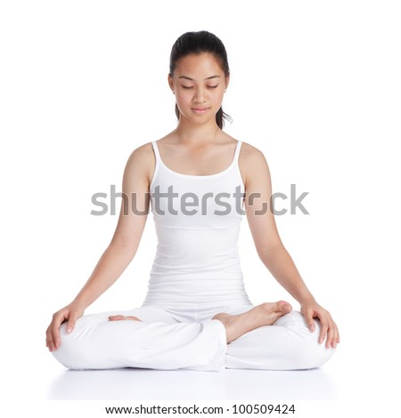 female asian teenager doing meditation against white background - stock photo
