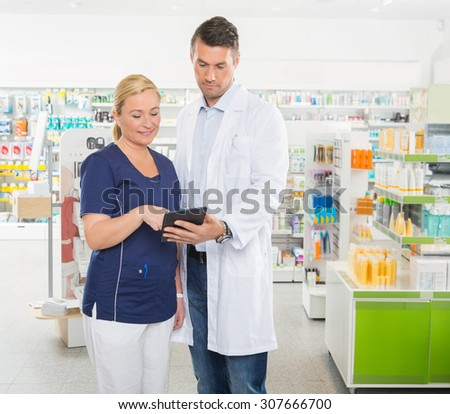 Female assistant using digital tablet with male pharmacist while standing in pharmacy - stock photo