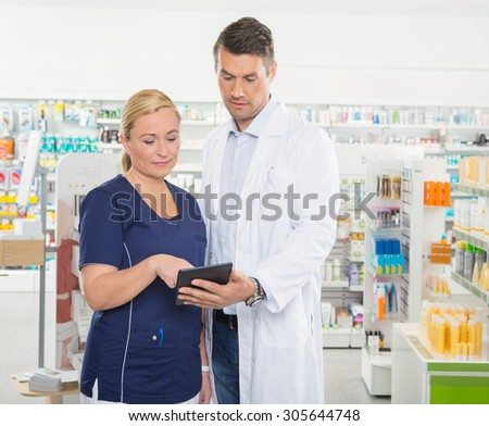 Female assistant using tablet computer with male pharmacist while standing in pharmacy - stock photo