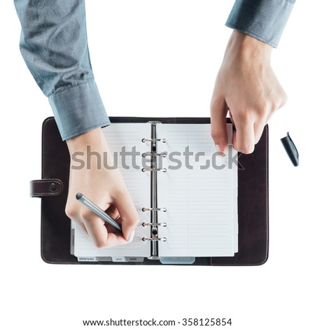 Female assistant writing schedule in a open planner pages hands close up, top view - stock photo
