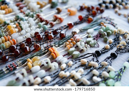 Female assortment accessory necklace and trinket on shop counter with shallow depth of field - stock photo