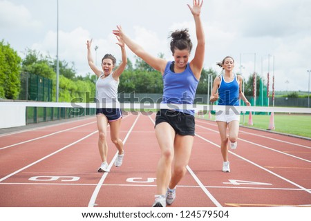 Female athlete celebrates win at finish line at track field - stock photo