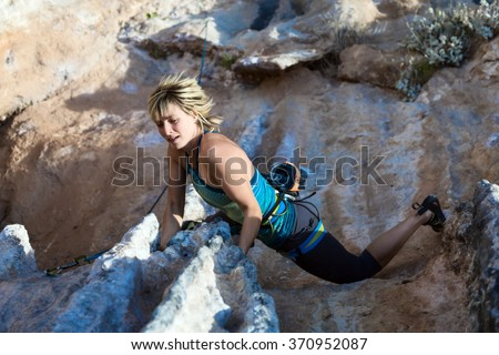Female Athlete climbing natural rock keeping hold and hanging over deep abyss