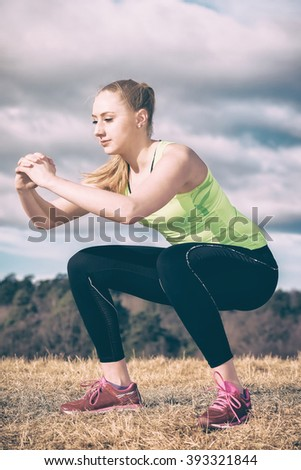 Female athlete exercises with squats outside in sunny weather. Filters applied - stock photo