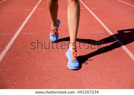 Female athlete feet running on the running track on a sunny day
