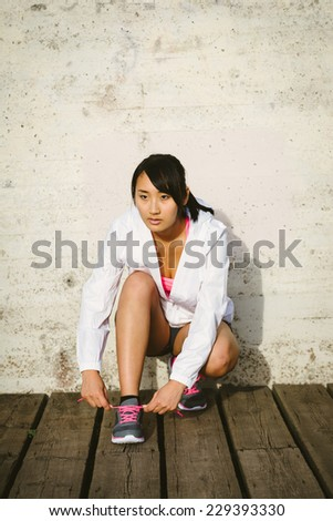 Female athlete getting ready for running training. Asian woman tying sport footwear laces. Sport and healthy lifestyle concept. Chinese beautiful sporty model. - stock photo