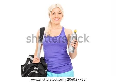 Female athlete holding a water bottle and carrying a sports bag isolated on white background - stock photo