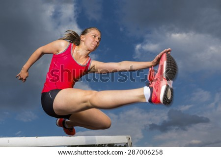 female athlete hurdling in track and field - stock photo