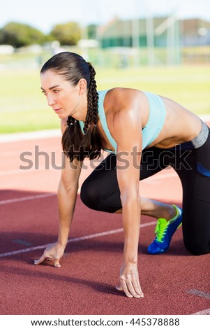 Female athlete in ready to run position on running track - stock photo