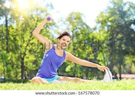 Female athlete in sportswear exercising with dumbbell in a park - stock photo