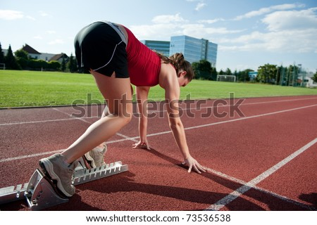 Female athlete in the starting blocks, ready to go - stock photo