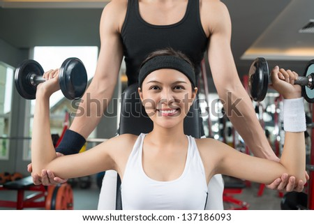Female athlete lifting dumbbells to strengthen her hands, her trainer supporting her
