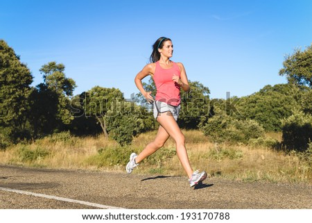 Female athlete on running workout in country road . Fitness sporty female runner training on summer.