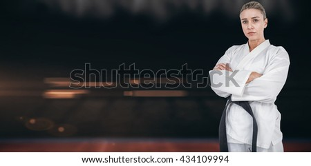 Female athlete posing in kimono against composite image of playing field indoor