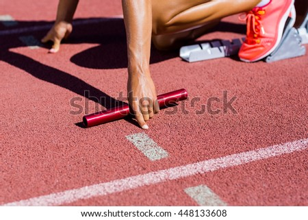 Female athlete ready to start the relay race on the running track - stock photo