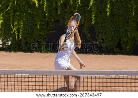 Female athlete returning ball. Young woman playing tennis swinging racket returning ball orange clay ground white dress with miniskirt green fence on background