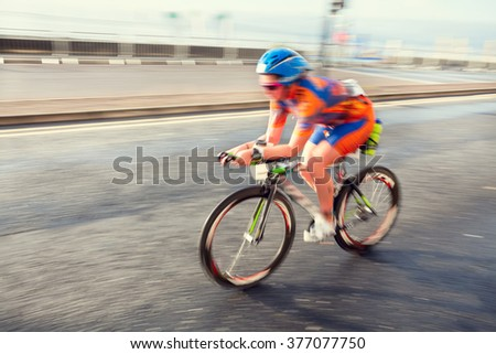 Female athlete riding bicycle at sunny day on coastal road, blurred motion - stock photo