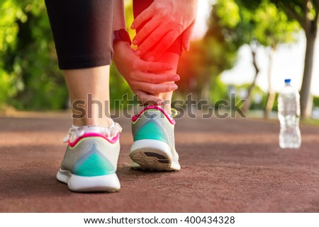 Female athlete runner touching foot in pain,closeup, fitness woman running in summer park. Healthy lifestyle and sport concept - stock photo