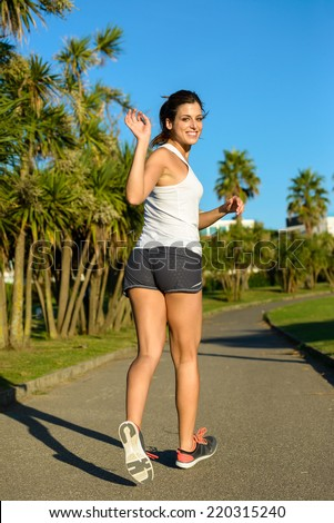 Female athlete running and waving outdoor in a park on summer. Brunette woman training and exercising. - stock photo
