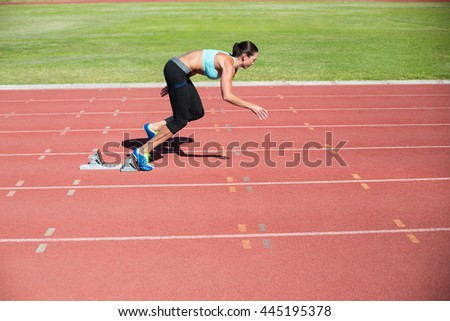 Female athlete running from starting blocks on running track - stock photo