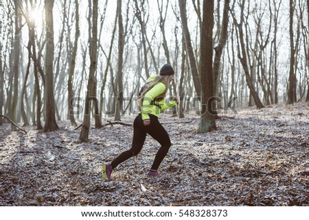 Female athlete running in the forest trail, healthy life concept