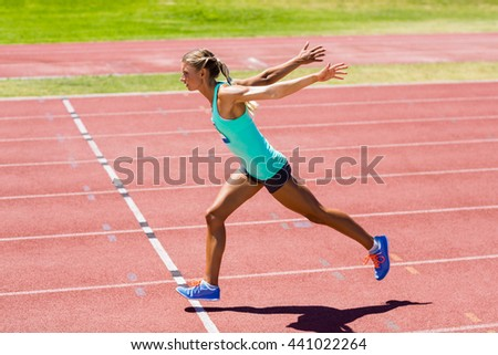Female athlete running on the racing track on a sunny day