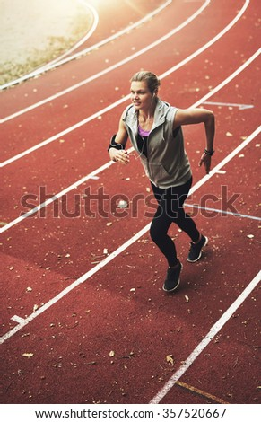 Female athlete running on track field while listening to music