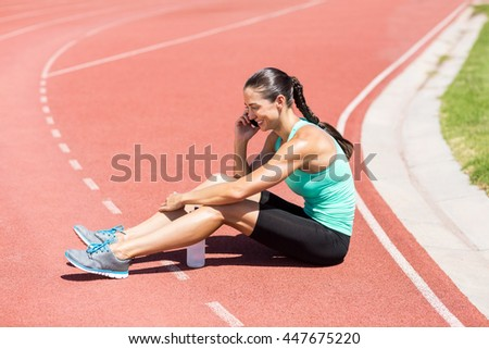 Female athlete sitting on running track and talking on mobile phone - stock photo