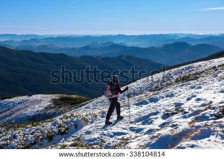Female Athlete Sport Clothing carrying Backpack Walking Up Mountain Peaks Sunlight Sky Majestic Summits Background - stock photo