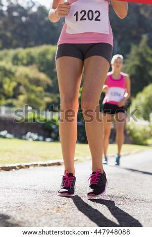 Female athlete standing on running track in park - stock photo