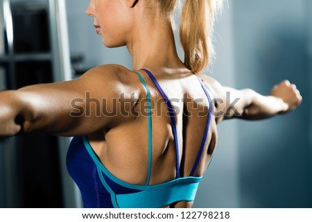 female athlete straining back muscles and arms, do sport in the fitness club - stock photo
