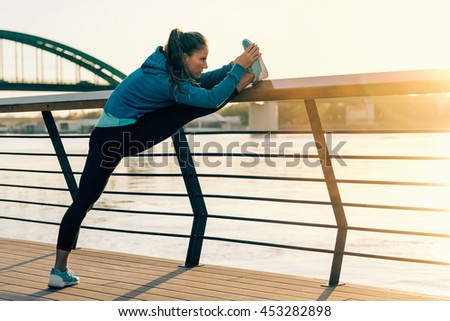 Female athlete streching outdoors by the riverside - stock photo