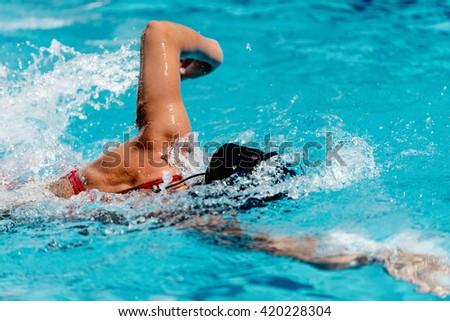 Female athlete swimming front crawl - stock photo