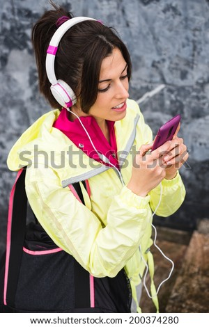 Female athlete texting sms with smartphone and relaxing after gym workout. Relaxed fitness woman leaning on a wall taking a break while looking her cellphone and listening music. - stock photo