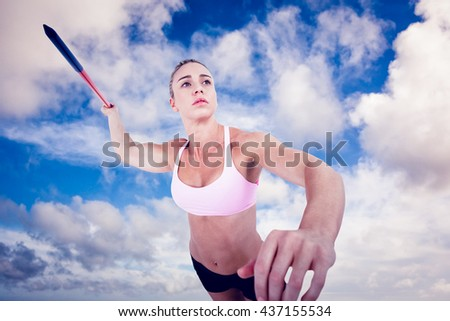 Female athlete throwing a javelin against blue sky with white clouds