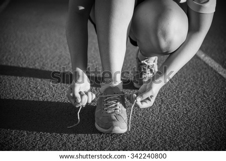 Female athlete tying laces for jogging , sunset , black and white