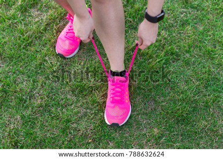 Female athlete tying running shoes for jogging. Runner getting ready for training. Sport lifestyle.