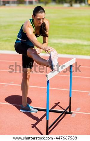 Female athlete warming up above hurdle on running track - stock photo