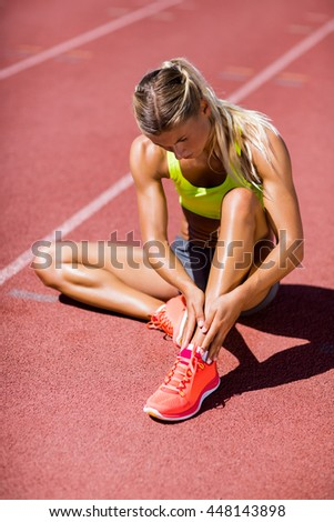 Female athlete warming up on the running track on a sunny day - stock photo