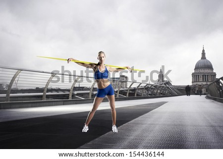 Female Athlete with javelin standing in front of St Paul's Cathedral in London - stock photo