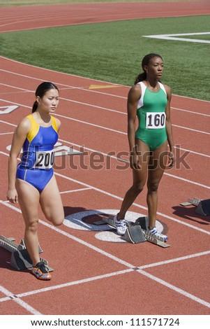 Female athletes at starting blocks on race track - stock photo