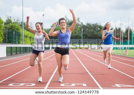 Female athletes celebrating as they cross finish line on track field - stock photo