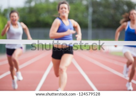 Female athletes close to finish line at track field - stock photo
