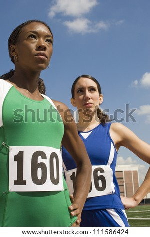 Female athletes in sportswear against sky - stock photo
