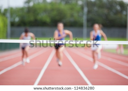 Female athletes running towards finish line on track field - stock photo